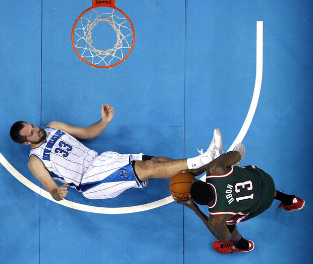 New Orleans Hornets forward Ryan Anderson (33) falls to the court as Milwaukee Bucks forward Ekpe Udoh (13) drives to the basket in the second half of an NBA basketball game in New Orleans, Monday, Dec. 3, 2012. The Hornets won 102-81. (AP Photo/Gerald Herbert)