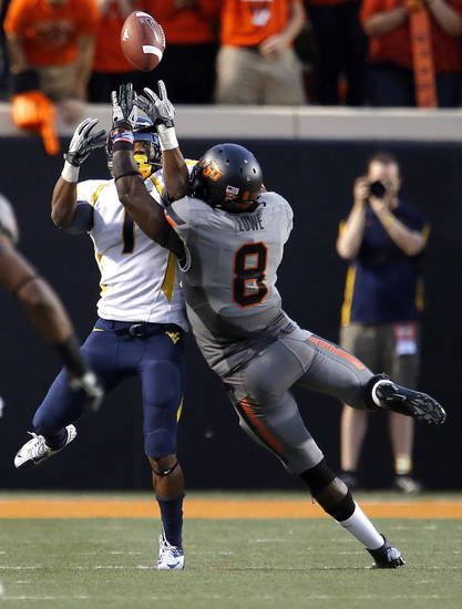 Oklahoma State's Daytawion Lowe (8) breaks up a pass intended for West Virginia's Tavon Austin (1) during a college football game between Oklahoma State University (OSU) and the West Virginia University at Boone Pickens Stadium in Stillwater, Okla., Saturday, Nov. 10, 2012. Photo by Sarah Phipps, The Oklahoman