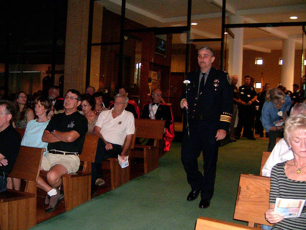 Johnny Kuhlman, Oklahoma City deputy police chief, walks toward the altar with a flower during the Blue Mass held recently at St. John the Baptist Catholic Church in Edmond. <strong>STEVE GUST - STEVE GUST</strong>