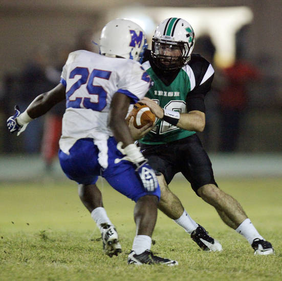 Camden Tharp (12) of Bishop McGuinness keeps the ball as Sheldon Bulock (25) of Millwood defends during a high school football game between Millwood and Bishop McGuinness at Bishop McGuinness Catholic High School in Oklahoma City, Friday, Sept. 16, 2011. Photo by Nate Billings, The Oklahoman