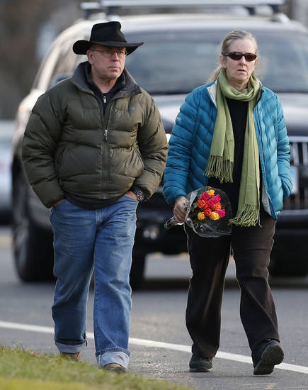 People walk with flowers toward a makeshift memorial a day after a gunman opened fire at an elementary school, Saturday, Dec. 15, 2012, in Newtown, Conn. The man, who died from a self-inflicted wound, allegedly killed his mother at their home and then opened fire Friday inside the Sandy Hook Elementary school, massacring 26 people, including 20 children. (AP Photo/Julio Cortez) ORG XMIT: CTJC137