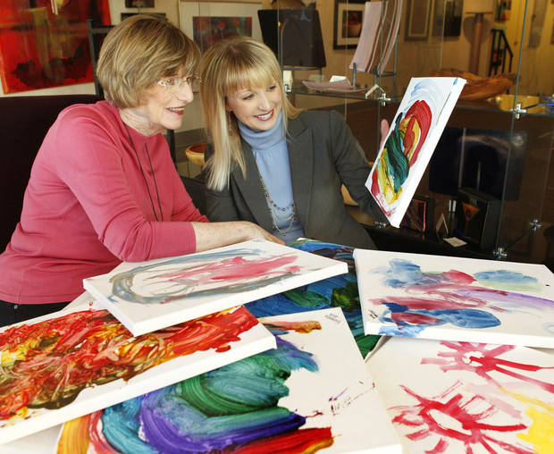 Sue Hale, left, who's paintings will be featured in a new exhibit to raise funds for EduCare, looks with Kelli Dupuy at some children's artwork at her studio in the Paseo district in Oklahoma City, OK, Monday, October 29, 2012,  By Paul Hellstern, The Oklahoman
