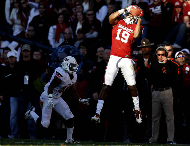 Oklahoma's Justin Brown (19) catches a pass in front of Oklahoma State's Brodrick Brown (19) during the Bedlam college football game between the University of Oklahoma Sooners (OU) and the Oklahoma State University Cowboys (OSU) at Gaylord Family-Oklahoma Memorial Stadium in Norman, Okla., Saturday, Nov. 24, 2012. Oklahoma won 51-48. Photo by Bryan Terry, The Oklahoman