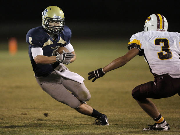 Heritage Hall's Kellen Stadler (1) runs the ball past Clinton's Bowman Vowell (3) during a high school football game between Heritage Hall and Clinton in Oklahoma City, Friday, Sept. 7, 2012.  Photo by Garett Fisbeck, The Oklahoman