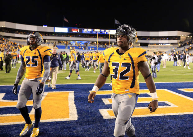 West Virginia's Ryan Clarke (32) and Darwin Cook (25) walk off the field after their NCAA college football game against TCU in Morgantown, W.Va., on Saturday, Nov. 3, 2012. TCU won 39-38 in overtime. (AP Photo/Christopher Jackson) ORG XMIT: WVCJ121