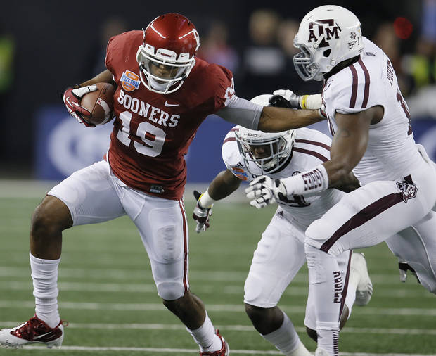 Oklahoma's Justin Brown (19) stiff arms Texas A&M's Sean Porter (10) during the college football Cotton Bowl game between the University of Oklahoma Sooners (OU) and Texas A&M University Aggies (TXAM) at Cowboy's Stadium on Friday Jan. 4, 2013, in Arlington, Tx. Photo by Chris Landsberger, The Oklahoman
