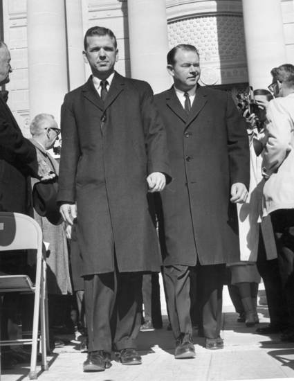 Gov. George Nigh escorts a winking Henry Bellmon to the platform for Bellmon's swearing in ceremony on January 14, 1963.  Nigh had been governor for a week following the resignation of J. Howard Edmondson but Bellmon, a Republican, had been elected the new Governor of Oklahoma by state voters the previous November.   Staff photo by Cliff King taken 1/14/63.