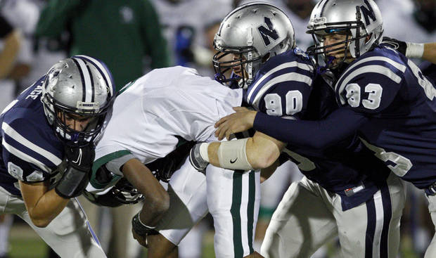 Edmond Santa Fe's Brandon Reece is brought down by Edmond North's  Jarech Page, left, Nick Washburn, and Nic Imel during a high school football game at Wantland Stadium in Edmond, Okla., Friday, Oct. 29, 2010.  Photo by Bryan Terry, The Oklahoman