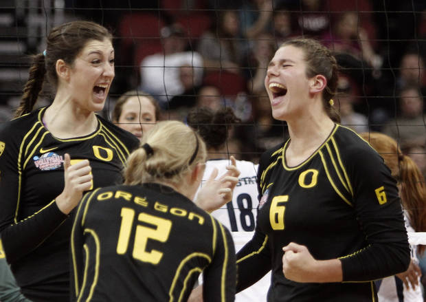 Oregon players Canace Finley, left, Katherine Fischer (12), and Liz Brenner (6) celebrate a second game victory over Penn State in the national semifinals of the NCAA college women's volleyball tournament semifinal in Louisville, Ky., Thursday, Dec. 13, 2012.  (AP Photo/Garry Jones)