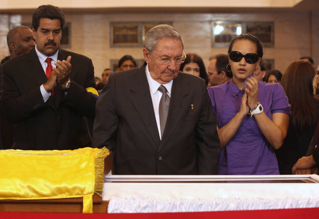 In this photo released by Miraflores Press Office,  Cuba's President Raul Castro looks at the body of  Venezuela's late President Hugo Chavez during his wake at a military academy where his remains will lie in state until his funeral in in state in Caracas, Venezuela, Thursday, March 7, 2013.  Nicolas Maduro, Venezuela's acting president, said Chavez's  remains will be put on permanent display at the Museum of the Revolution, close to the presidential palace where Chavez ruled for 14 years. A state funeral for Chavez attended by some 33 heads of government is scheduled to begin Friday morning.  At right is Chavez's daughter Rosa Virginia Chavez and left is Vice-President Nicolas Maduro.(AP Photo/Miraflores Press Office)