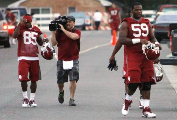 Film crews document the 6:45 a.m. arrival of Ryan Broyles (85) as he heads to the University of Oklahoma (OU) Sooners first practice on Thursday, August 4, 2011, in Norman, Okla.  At right is offensive tackle Donald Stephenson (59). Photo by Steve Sisney, The Oklahoman