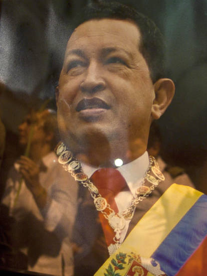 People are seen refelcted on an image of Venezuela's President Hugo Chavez during a mass in support of him in Havana, Cuba, Thursday, Dec. 13, 2012. Chavez is recovering favorably despite suffering complications during cancer surgery in Cuba, his vice president Nicolas Maduro said Thursday amid uncertainty over the Venezuelan leader's health crisis and the country's political future. (AP Photo/Ramon Espinosa)