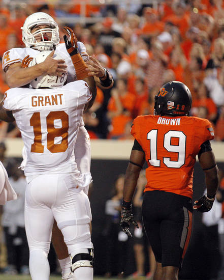 Texas' David Ash (14) and D.J. Grant (18) celebrate a touchdown in froth of Oklahoma State's Brodrick Brown (19) during a college football game between Oklahoma State University (OSU) and the University of Texas (UT) at Boone Pickens Stadium in Stillwater, Okla., Saturday, Sept. 29, 2012. Photo by Sarah Phipps, The Oklahoman