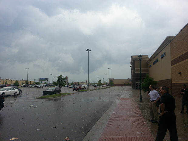 Best Buy employees and customers look at the damage from the tornado after emerging from an interior room in the store. Photo by Caleb McWilliams