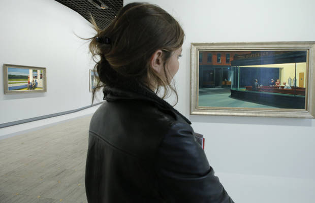 "A woman looks at ""Nighthawks, 1942"", at right, as part of the retrospective of Edward Hopper, one of the great American 20th century artists at Paris� Grand Palais Museum, in Paris, Monday, Oct. 8, 2012. This major Hopper retrospective reveals that the 20th century painter known for his rendering of American life, also drew inspiration from France, and includes some 128 Hopper works, such as the masterpieces �Nighthawks� and �Soir Bleu�.(AP Photo/Francois Mori)"