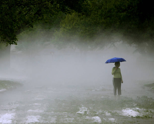 Walking through fog created by the hail and warm temperatures, Louise Vandaveer walks past debris on Huntleigh Street in The Village as she checks on her neighbors following a storm in the Oklahoma City metro area on Sunday, May 13, 2010. By John Clanton, The Oklahoman