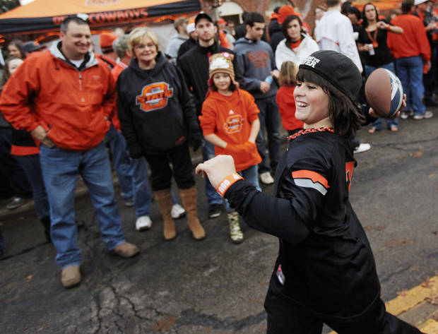 OSU fan Karsten Menard, 11, of Edmond, Okla., throws the football with friend and OU fan Jace Rosser, (not pictured), 12, of Edmond also, while waiting for the start of the Spirit Walk before the Bedlam college football game between the Oklahoma State University Cowboys (OSU) and the University of Oklahoma Sooners (OU) at Boone Pickens Stadium in Stillwater, Okla., Saturday, Dec. 3, 2011. Photo by Nate Billings, The Oklahoman