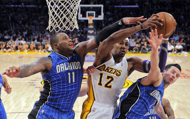 Los Angeles Lakers center Dwight Howard, center, goes up for a shot as Orlando Magic forward Glen Davis, left, and guard J.J. Redick defend during the second half of their NBA basketball game, Sunday, Dec. 2, 2012, in Los Angeles. The Magic won 113-103. (AP Photo/Mark J. Terrill)
