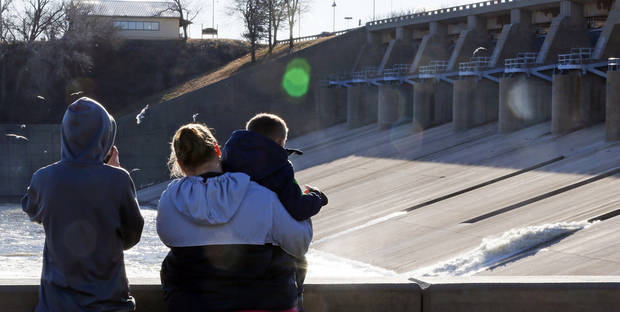 Top: Canton residents, from left, Tyler Pope, 13, April Pope, and Tenyr Pope, 5, watch water flow from the spillway Wednesday. PHOTOS BY NATE BILLINGS, THE OKLAHOMAN