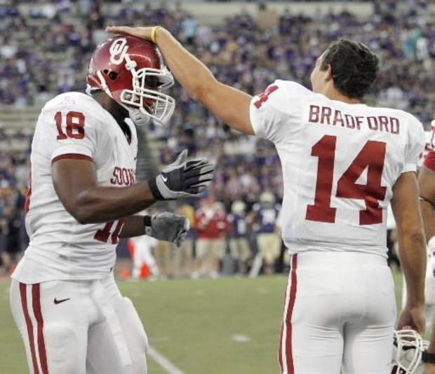 OU quarterback Sam  Bradford pats Jermaine  Gresham (18) on the helmet after the two connected for a touchdown in the third quarter during the college football game between the University of Oklahoma (OU) and Washington at Husky Stadium in Seattle, Wash., Saturday, September 13, 2008. OU beat UW, 55-14. BY NATE BILLINGS