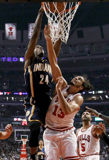 Indiana Pacers forward Paul George (24) dunks over Chicago Bulls center Joakim Noah (13) during the first half of an NBA basketball game Tuesday, Dec. 4, 2012, in Chicago. (AP Photo/Charles Rex Arbogast)