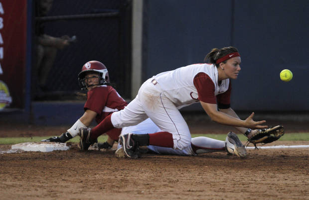 Oklahoma's Lauren Chamberlain (44) slides into third base past Alabama's Courtney Conley (9) during a Women's College World Series game between OU and Alabama at ASA Hall of Fame Stadium in Oklahoma City, Monday, June 4, 2012.  Photo by Garett Fisbeck, The Oklahoman