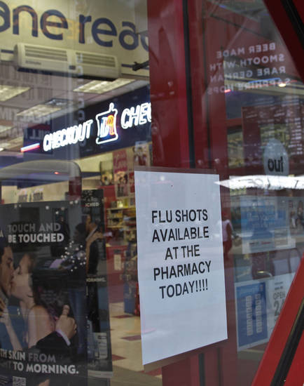 A sign on a pharmacy window announce flu shots availability, Monday, Jan. 14, 2013 in New York.   Some New York City pharmacies and clinics are reporting flu vaccine shortages caused by reports of widespread outbreaks, but the city's Health Department said  shortages are in individual locations and don't reflect a larger supply problem.  (AP Photo/Bebeto Matthews)