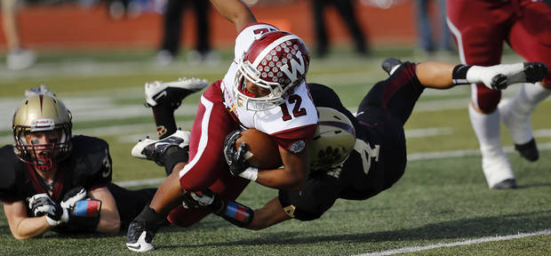 Wynnewood runningback Curtis Rushing is brought to the turf by Peyton Maroney.  Defender at left is Hunter Suntken.  Cashion vs. Wynnewood at Norman in a Class A semifinal football game, Saturday, Dec. 1, 2012.     Photo by Jim Beckel, The Oklahoman
