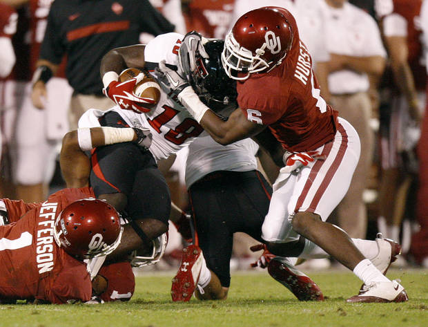 Oklahoma&#039;s Demontre Hurst (6) and Tony Jefferson (1) bring down Texas Tech&#039;s Eric Ward (18) during the college football game between the University of Oklahoma Sooners (OU) and the Texas Tech University Red Raiders (TTU) at Gaylord Family-Oklahoma Memorial Stadium in Norman, Okla., Saturday, Oct. 22, 2011. Photo by Bryan Terry, The Oklahoman