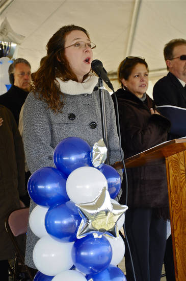 Jennifer Hogan sings the national anthem during an AWACS replica dedication.