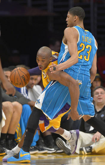 Los Angeles Lakers guard Kobe Bryant, left, moves around New Orleans Hornets forward Anthony Davis during the first half of an NBA basketball game, Tuesday, Jan. 29, 2013, in Los Angeles. (AP Photo/Mark J. Terrill)