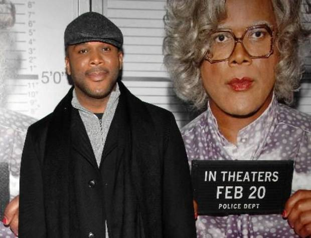 Tyler Perry standing in front of a Madea movie poster