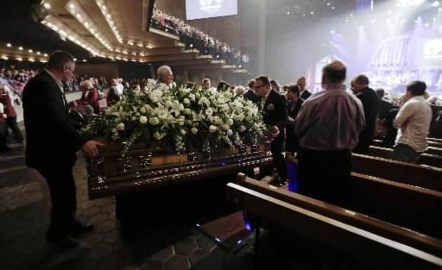 Attendees stand as the casket of country music star George Jones is taken out of the Grand Ole Opry House following his funeral on Thursday, May 2, 2013, in Nashville, Tenn. Jones, one of country music's biggest stars who had No. 1 hits in four separate decades, died April 26. (AP)