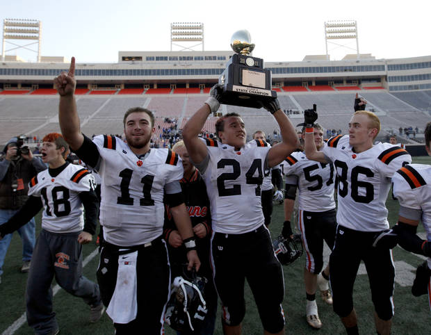 CLASS A HIGH SCHOOL FOOTBALL STATE CHAMPIONSHIP / CELEBRATION: Wayne's Josh Way holds up the championship trophy as Sam Martin (11) and Justin Rafferty (86) celebrate after defeating Woodland in the  Class A state championship high school football game at Boone Pickens Stadium in Stillwater, Okla., Saturday, Dec. 10, 2011. Photo by Sarah Phipps, The Oklahoman
