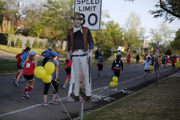 Runners pass a poster of John Wayne on Shartel as they approach Gorilla Hill during the Oklahoma City Memorial Marathon in Oklahoma City, Sunday, April 28, 2013.  Photo by Garett Fisbeck, For The Oklahoman
