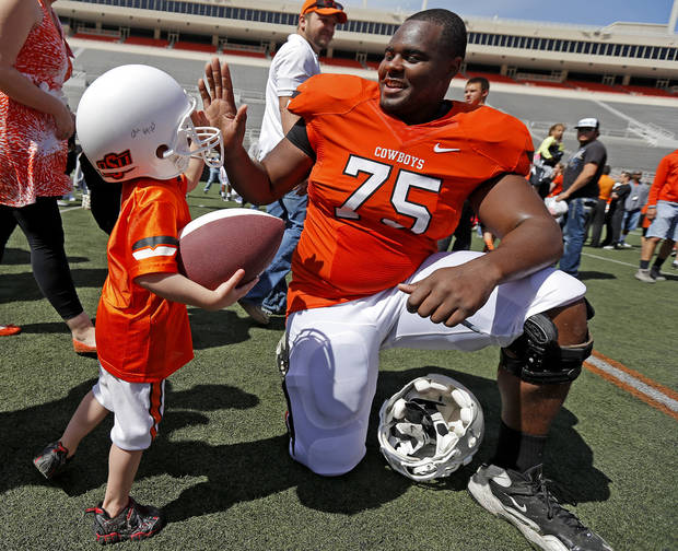 Keeton Metcalf, 3, of Stillwater, slaps hands with Oklahoma State's Chris Grisbhy after OSU's spring football game at Boone Pickens Stadium in Stillwater, Okla., Sat., April 20, 2013. Photo by Bryan Terry, The Oklahoman