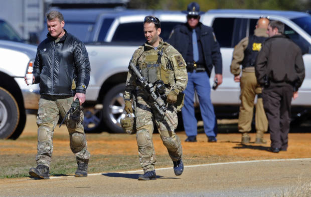 Law officers at the Dale County hostage scene in Midland City, Ala. on Thursday morning, Jan. 31, 2013. A gunman holed up in a bunker with a 6-year-old hostage has kept law officers at bay since the standoff began when he killed a school bus driver and dragged the boy away, authorities said. (AP Photo/Montgomery Advertiser, Mickey Welsh)