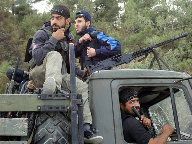 In this Sunday October 7, 2012 citizen journalism image provided by Edlib News Network, ENN, which has been authenticated based on its contents and other AP reporting, Free Syrian Army fighters sit on top of a military truck that was captured from the Syrian Army in the village off Khirbet al-Jouz, in the northern province of Idlib, Syria. The Turkish state-run Anadolu news agency said Sunday that the rebels had regained full control of Khirbet al-Jouz. (AP Photo/Edlib News Network ENN)