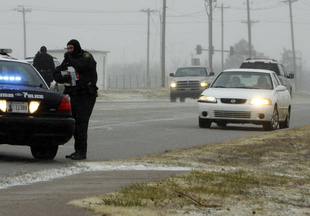 Norman police respond to a two-car accident on North Flood south of Tecumseh as rain, sleet, high winds and freezing temperatures move into the area on Thursday, Dec. 24, 2009, in northwest Norman, Okla.   One vehicle sits southbound on the northbound lanes.  Photo by Steve Sisney, The Oklahoman