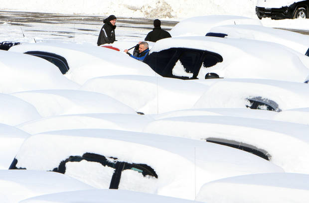Workers at a car dealership on Route 6 in Carmel, N.Y. clean snow from the cars in their lot, Saturday, Feb. 9, 2013. The year's first major winter storm dumped up to 21 inches on the Lower Hudson Valley.  (AP Photo/The Journal News, Frank Becerra Jr.) NYC OUT, NO SALES, ONLINE OUT, TV OUT, NEWSDAY INTERNET OUT; MAGS OUT