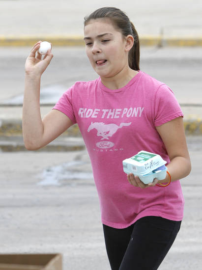 Brannah Talamantes, 11, throws an egg filled with paint at a piece of paper during an art activity at the Almonte Library. Such activities will continue throughout the summer. Photo By Steve Gooch, The Oklahoman <strong>Steve Gooch - The Oklahoman</strong>