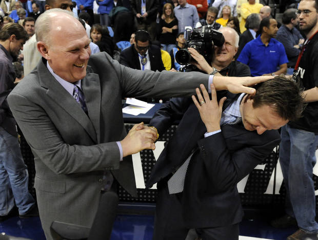 Denver Nuggets head coach George Karl, left, jokes with Oklahoma City Thunder head coach Scott Brooks before the start of game 4 of a first-round NBA basketball playoff series Monday, April 25, 2011, in Denver. (AP Photo/Jack Dempsey)
