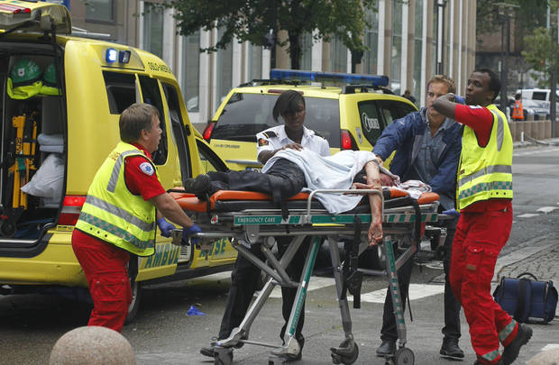 A victim is carried to a waiting ambulance in central Oslo, Friday July 22, 2011, following an explosion that tore open several buildings including the prime minister's office, shattering windows and covering the street with documents.(AP Photo/Berit Roald, Scanpix, Norway)