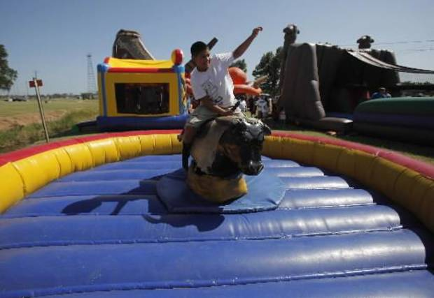 Austin Blythe, 13, of Earlsboro, rides a mechanical bull at a Fourth of July Celebration in Seminole, Okla., July 4, 2012. Photo by Garett Fisbeck, The Oklahoman