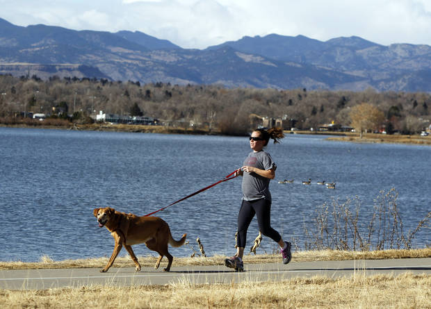 This photo taken on Dec. 7, 2012 shows Rachel Gardner jogging with her dog Allie at Sloan's Lake in Denver. Get a panoramic view of the mountains and a good hike without leaving the Denver sunbelt at this 177-acre lake on the far western edge of Denver. (AP Photo/Ed Andrieski)