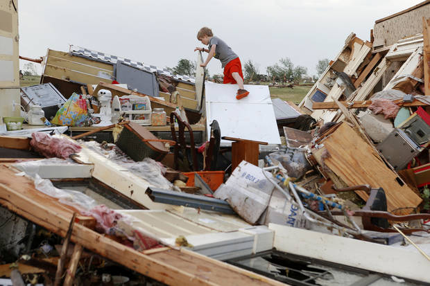 Campbell Miller, 10, looks through the home of his grandmother, Marlena Hodson, after a tornado damaged her home in Carney Okla., Sunday, May 19, 2013. Hodson and her family left the home to escape the tornado. Photo by Bryan Terry, The Oklahoman