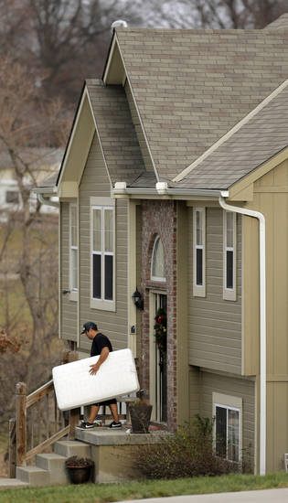 An unidentified man carries items out of a Kansas City home shared by Kansas City Chiefs linebacker Jovan Belcher and his 22-year-old girlfriend Kasandra Perkins, Monday, Dec. 3, 2012. Belcher shot and killed Perkins at their home Saturday before driving to Arrowhead Stadium, where Belcher committed suicide in the practice facility's parking lot after meeting with head coach Romeo Crennel and general manager Scott Pioli, police said. (AP Photo/Charlie Riedel)