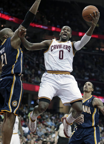 Cleveland Cavaliers' C.J. Miles (0) jumps to the basket against Indiana Pacers' David West (21) during the second quarter of an NBA basketball game on Friday, Dec. 21, 2012, in Cleveland. (AP Photo/Tony Dejak)
