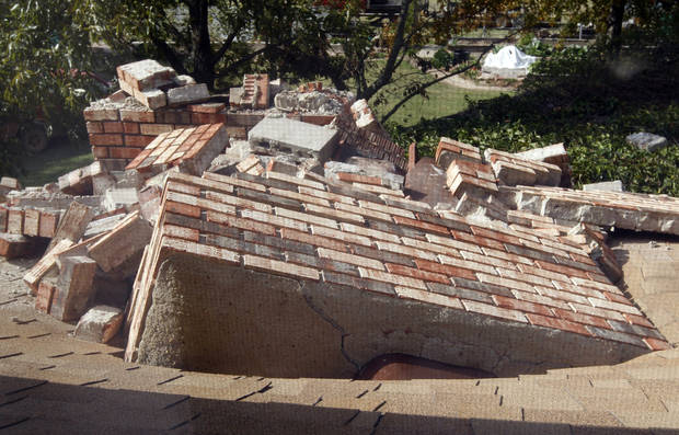 Pieces of a chimney that toppled and went through the roof at the home of Joe and Mary Reneau are pictured from a second-story window in Sparks, Okla., Sunday, Nov. 6, 2011. The chimney was damaged in Saturday night's earthquake. (AP Photo/Sue Ogrocki) ORG XMIT: OKSO109