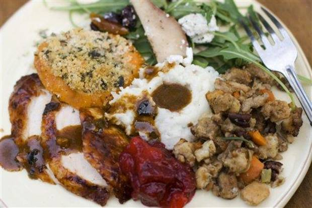 In this image taken on Oct. 8, 2012, a Thanksgiving dinner plate of cider brined turkey with sage gravy, peach cranberry sauce, sour cream and chive mashed potatoes, sausage pecan stuffing, arugula pear salad with pomegranate vinaigrette and goat cheese and herb crusted sweet potatoes is shown in Concord, N.H. (AP Photo/Matthew Mead)